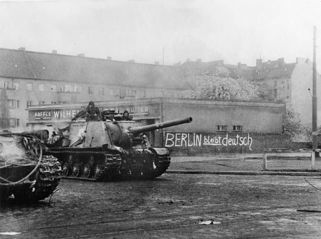 "After the battle ended, Soviet tanks patrol a Berlin street. The graffiti says, ironically, ""Berlin will remain German."""
