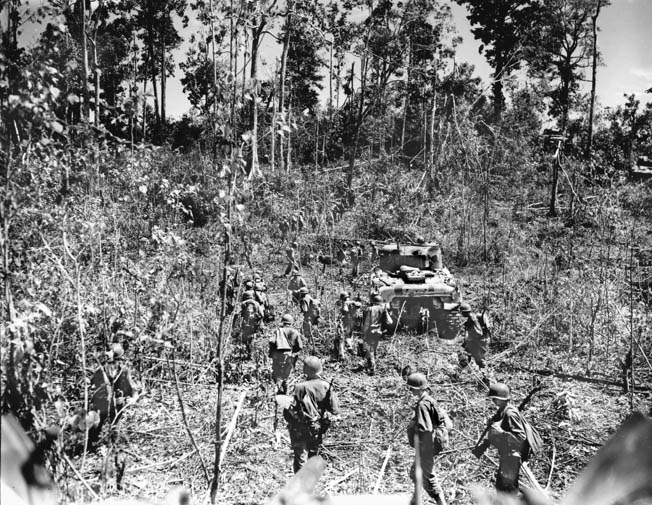 American infantrymen and supporting Sherman tanks advance through the jungle of Biak near Mokmer airstrip in June 1944. The Japanese who occupied the island put up a tenacious defense, fortifying many caves on the island and forcing the Americans to root them out or seal them inside with explosives.