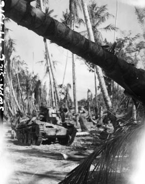 Knocked out by an American Sherman tank during one of the few armor versus armor encounters of the Pacific War, the hulk of a Japanese light tank smolders on Biak. The Japanese tanks mounted 37mm guns that were capable of inflicting only limited damage on the Shermans, while the American tanks mounted heavier 75mm guns with greater penetrating power.