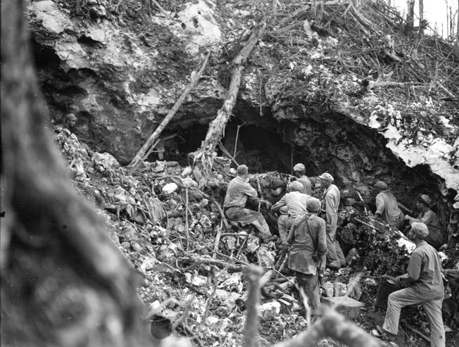 After retreating from a barrage of Japanese hand grenades, American combat engineers return to the mouth of a fortified Japanese cave on Biak. Often the engineers used satchel charges to seal the entrances to the many caves on the island, trapping the enemy occupants inside.