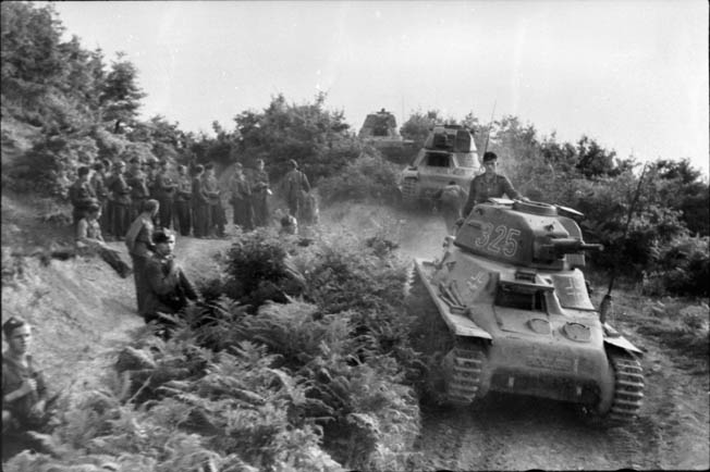 Tanks and troops of the German Army advance during the invasion of Yugoslavia. Among these German armored vehicles are three Hotchkiss tanks apparently captured during the invasion of France.