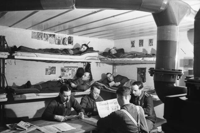 A propaganda photo shows a German battery crew relaxing in their concrete quarters inside a casemate.