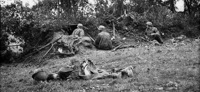 German parachute troops occupy a dugout in the French hedgerows in the presence of a dead American soldier.