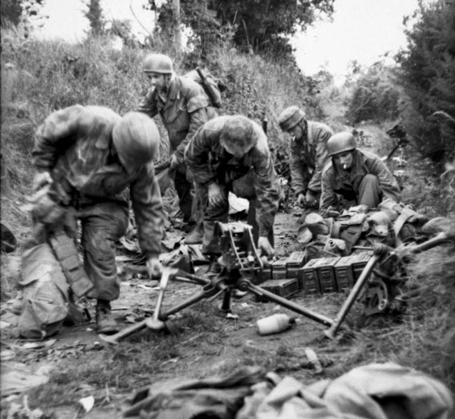German paratroopers in Normandy gather weapons as they prepare to shift to a new defensive position as the American advance. The Germans held strong positions on firm ground on the west side of Carentan.