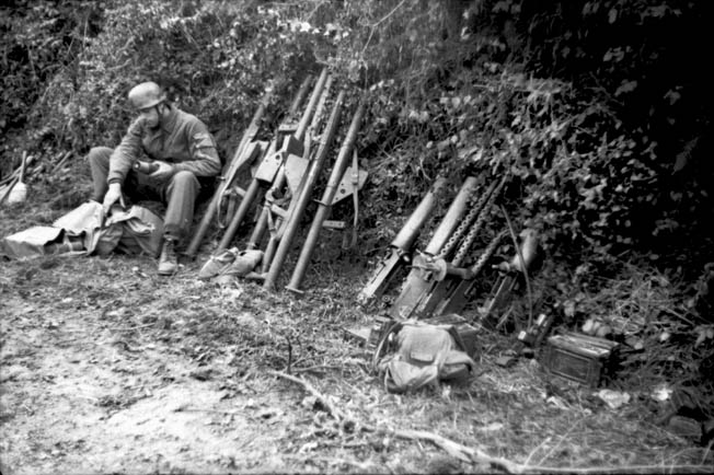 A German paratrooper, sitting in the lee of a hedgerow, prepares ammunition for several shoulder-fired antitank weapons. His arsenal also includes captured American machine guns.