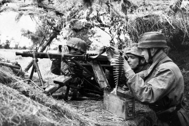 A German Fallschirmjäger MG42 machine-gun team, in their distinctive helmets and camouflage smocks, prepare for an American attack in Normandy. Hill 192 was defended by numerous machine-gun positions of the 3rd Fallschirmjäger Division.
