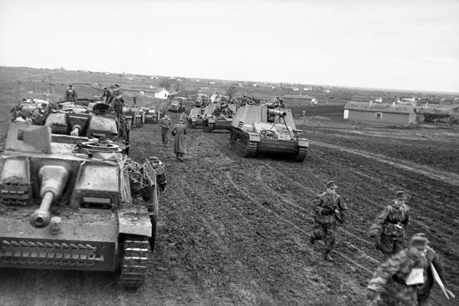 Traversing a muddy road on the outskirts of a Ukrainian village, two columns of German assault guns move toward the front lines. The vehicle to the left is the Sturmgeschütz III mounting a 75mm gun, and the vehicle on the right is the Hummel (Bumblebee) self-propelled 150mm howitzer.