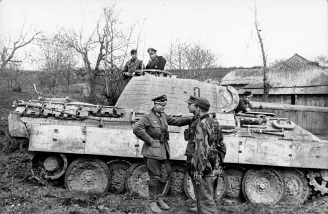 Colonel Karl Lorenz, who later rose to the rank of brigadier general and command of the Panzergrenadier Regiment Grossdeutschland, pauses alongside a PzKpfw. V Panther mediun tank to discuss upcoming movements with other officers. With its high-velocity 75mm cannon, the Panther constituted the German response to the legendary Soviet T-34 medium tank.