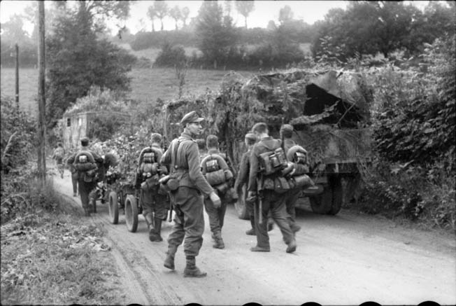 German troops advance toward the town of Breville, France, a week after the Allied invasion. British tanks and infantry failed to take and hold the town, and subsequently the Canadian paratroopers of the 1st Battalion joined in to secure the important objective.
