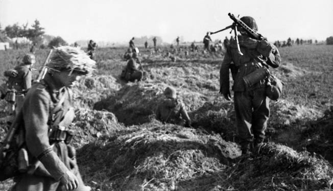 Panzergrenadiers of the Grossdeutschland Division of Army Group South emerge from trenches and strike out across the Russian steppe during Operation Citadel. One of the soldiers carries a light machine gun over his shoulder. Bundesarchiv Bild 101I-732-0135-22; Photo: Göttert