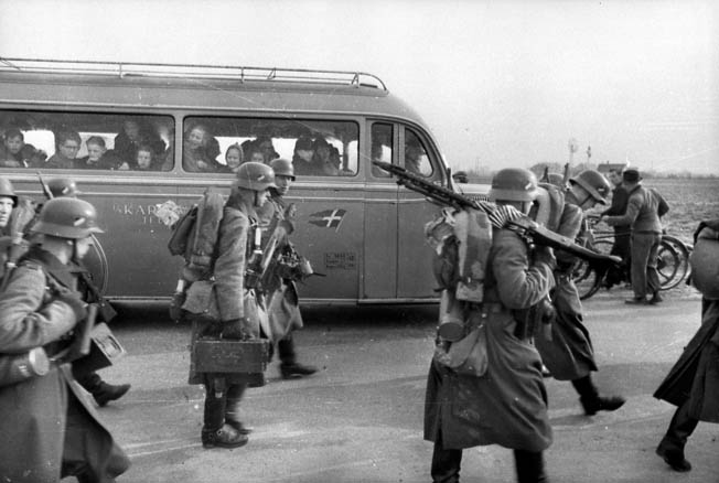 A busload of Danish school children watch in amazement as German troops march into Copenhagen, April 9, 1940. Danish defenses were overrun by the Germans in a matter of hours.