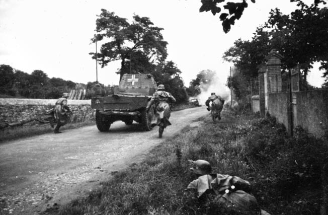 Well-trained and disciplined German troops rush down a dirt road in France with supporting armored vehicles close by. German troops were much better trained and equipped than their French adversaries in 1940.