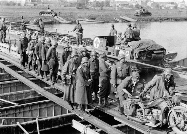 Troops from the 1st Panzer Division escort French prisoners across a pontoon bridge over the Meuse on May 14. Although some French troops gave a good account of themselves even after their lines were breached, many surrendered en masse.
