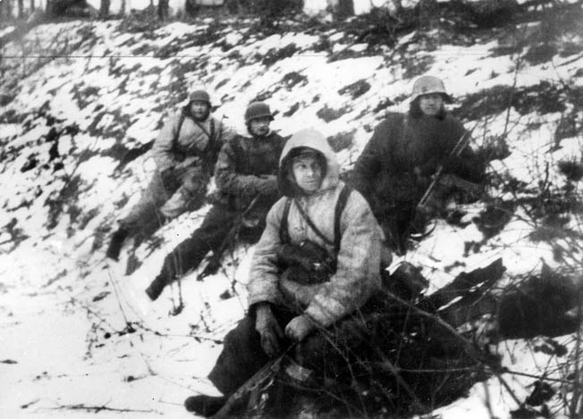 German soldiers, some of them camouflaged against the winter landscape, pause along a ravine during their retreat toward the Oder River. Entire German divisions disappeared during the initial Soviet attack.