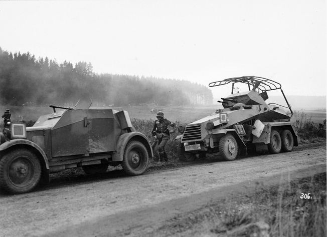 Reconnaissance troops participate in an exercise in 1936 with an SdKfz.13 open-topped armored scout car armed with an MG-13 machine gun and a SdKfz.232 six-wheeled heavy armored scout vehicle featuring a fully rotating turret with a 20mm autocannon and an MG-13 machine gun.