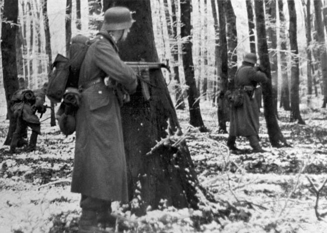 A German soldier with an STG-44 and his comrades move through snowy woods toward American lines in Luxembourg, shortly after the start of the offensive, December 1944.