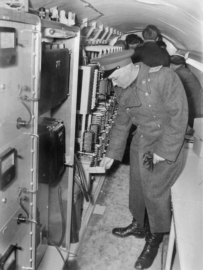 A Soviet officer shows reporters CIA electronic monitoring equipment during a press conference revealing the existence of the tunnel.