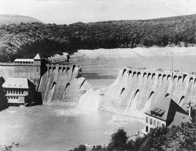 Water pours through the breach in the Eder Dam on the day following the Dambuster Raid. Air crews of RAF No. 617 Squadron completed the perilous mission aboard their Lancaster heavy bombers.