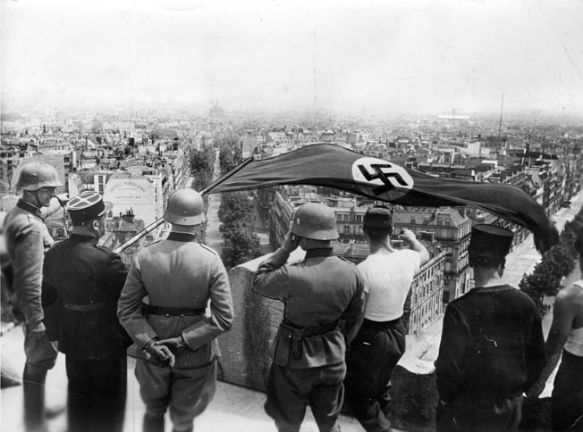 Standing atop the Arc de Triomphe in Paris, German soldiers and collaborationist French officials see to the raising of the swastika-emblazoned Nazi banner from one of the most recognizable symbols of French national pride. Paris endured four years of Nazi occupation before its liberation by the Allies in August 1944.