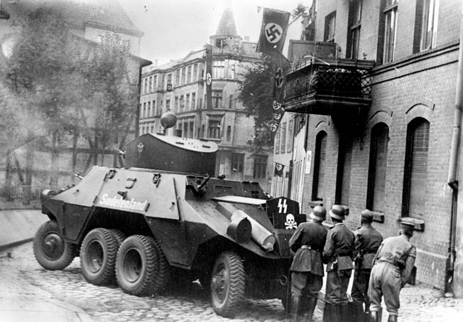 Soldiers of SS Heimwehr Danzig, an SS unit recruited in Danzig, take cover behind an ADGZ armored car during an attack on Polish troops in a post office. SS Heimwehr Danzig was incorporated into the 3rd SS Totenkopf Division after the Poland campaign.