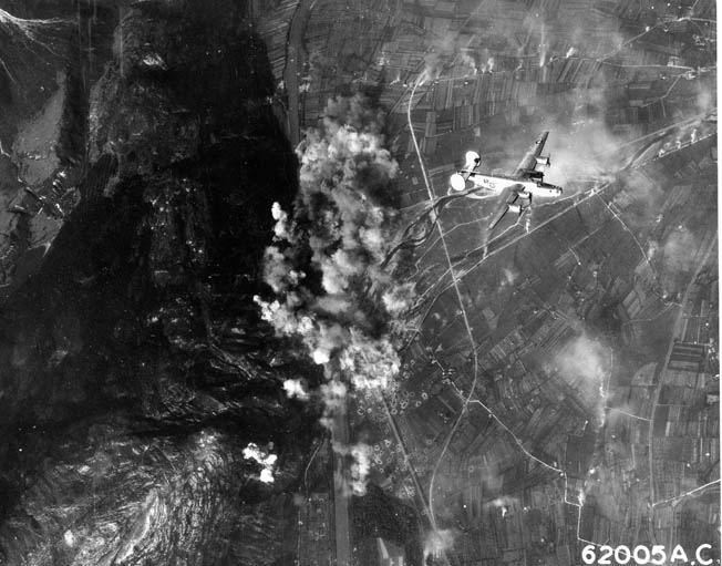 Smoke and dust rise as a B-24 Liberator flies high above a target during a raid over Germany. B-24s dropped over 450,000 tons of bombs on Europe during World War II.