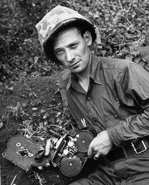 """Coast Guard cinematographer Charles W. Bossert shows off the damage to his Bell & Howell Eyemo 35mm movie camera caused by shrapnel from a Japanese mortar on Iwo Jima. Many combat photographers were killed or wounded while trying to get """"the shot"""" and visually document the war."""