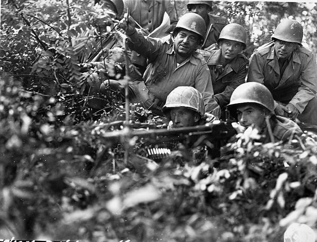Brigadier General Eyxlydes Zenobio da Costa (pointing), field commander of BEF Combat Team 11, poses with some of his troops manning a machine-gun position.