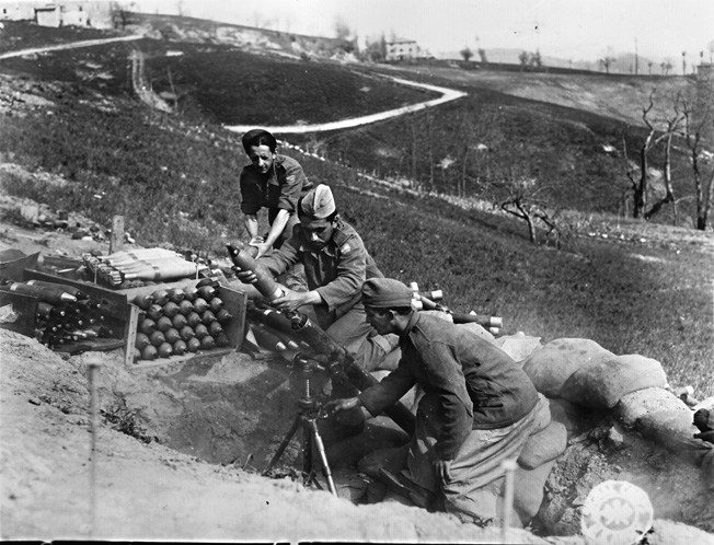 A Brazilian mortar crew fires their 81mm mortar in support of infantry in the Sassomolare area of the Fifth Army front north of Florence, April 1945.