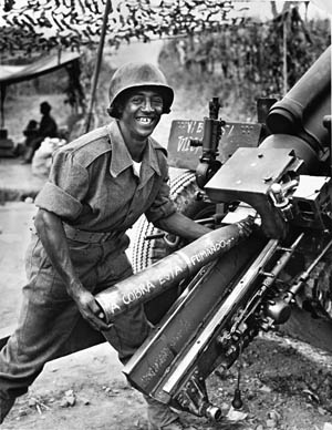 "A grinning Brazilian artilleryman in Italy loads a 105mm howitzer with a round inscribed with the troops' message for Hitler in Portuguese: ""The snake is fuming"" (angry). The Brazilian Expeditionary Force was part of the multinational Fifth U.S. Army in Italy."