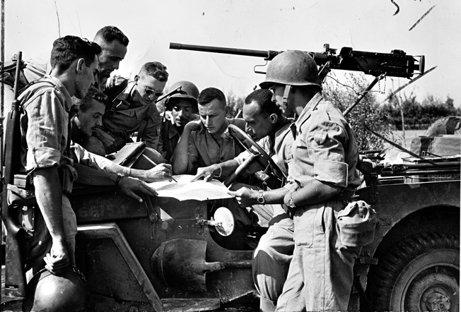 Company officers from the BEF study maps before attacking Germans along the Fifth Army front line in the Northern Apennines, October 1944.