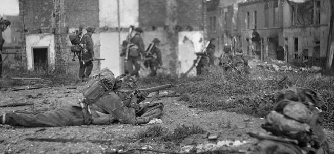 British assault troops advance through the rubble-strewn streets of Flushing.
