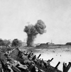 Artillery shells explode as British assault troops advance at dawn along the waterfront near Flushing, November 1, 1944.