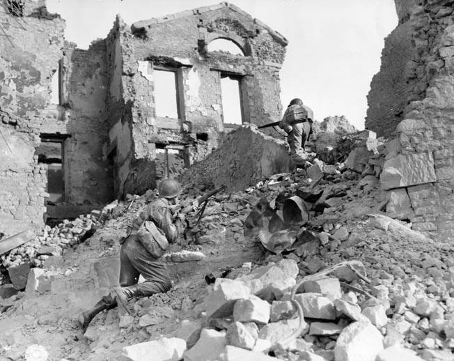 Members of an American engineer unit scramble over piles of rubble during the advance into Brittany, August 1944. Many French cities were destroyed or badly damaged during the fighting.