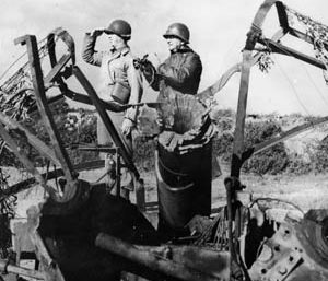 Brig. Gen. James A. Van Fleet, ADC of the 2nd Infantry Division, left, and Maj. Gen. Troy Middleton, VIII Corps commander, view battle from a destroyed German gun position.