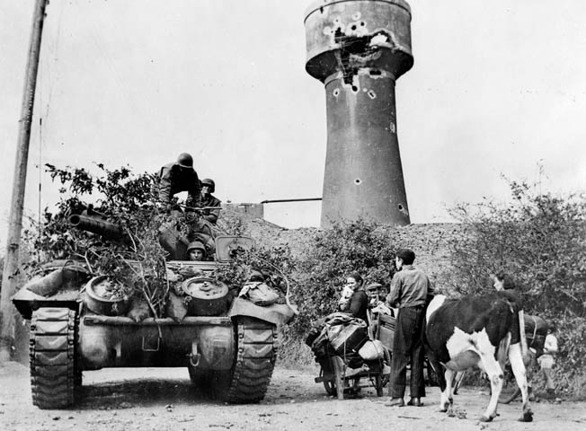 A French family, fleeing the battle area with their cow and meager belongings, watches an American tank destroyer, camouflaged with foliage, rumble by.