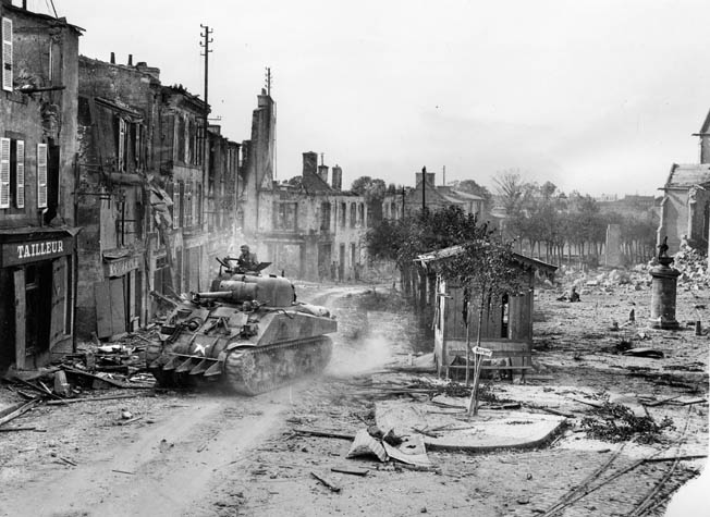 "A Sherman tank equipped with a ""hedge-buster"" welded to its front hull advances through the deserted streets of Lambezellic en route to Brest, August 1944."