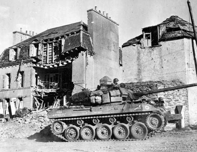 An American M-18 tank destroyer rolls through the shattered remains of a street in Brest.