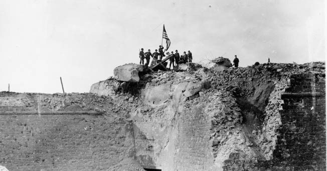 After the Citadel at St. Malo fell, GIs raise the American flag over an antiaircraft position atop the rubble, August 26, 1944.