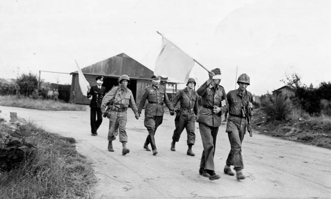 Blindfolded German officers are guided back to their lines after discussing surrender terms with American commanders, September 1944.