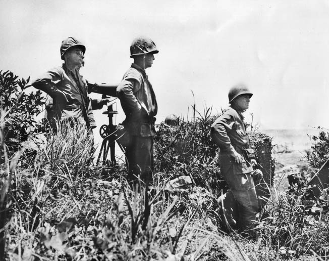Commander of U.S. ground forces, Lt. Gen. Simon Bolivar Buckner, Jr. (right), surveys the battlefield in this photo taken just minutes before he was killed by an enemy shell, June 18, 1945.