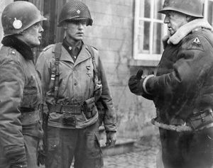 General George S. Patton (right) congratulates Brig. Gen. Anthony McAuliffe, the temporary commander of the 101st Airborne Division, and Lt. Col. Steve Chappius, the commander of 2nd Battalion, 502nd Parachute Infantry Regiment. General Patton gave them both Distinguished Service Crosses for successfully defending Bastogne.