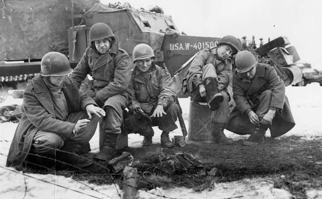 Antiaircraft gun crewmen from the 6th Armored Division and paratroopers from the 101st Airborne warm themselves by a fire while pulling on new overshoes after the relief of Bastogne.