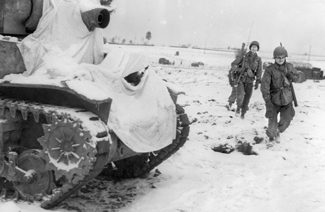 """Three """"Screaming Eagle"""" paratroopers pass a U.S. 75mm howitzer motor carriage that has been snow-camouflaged with white sheets. Once Lt. Gen. George S. Patton's Third Army reached Bastogne, Buford and his comrades received armor support."""