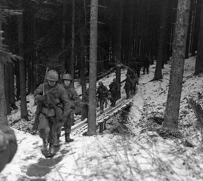 Men of the 106th Infantry Division on patrol in Belgian woods near the German border before the onslaught. The troops had not yet seen battle and much of the main thrust of the German counteroffensive fell squarely on their lines.