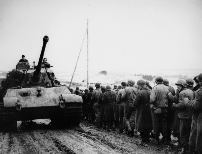 As a Tiger tank heads west, American prisoners captured early in the battle march toward POW camps in Germany.