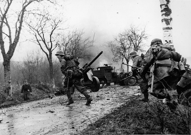 Troops of the 1st SS Panzer Division cross a road near Poteau, Belgium, strewn with the wreckage of American vehicles belonging to the 14th Armored Cavalry Group. The photo was staged for the photographer only hours after the Battle of the Bulge began. It was later found by American troops among captured equipment.