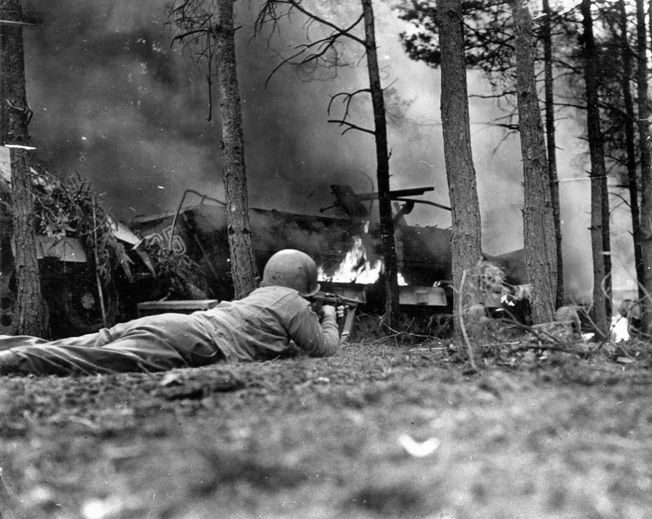 A GI trains his Thompson sub-machine gun on a burning German half-track near St. Vith early in the battle.