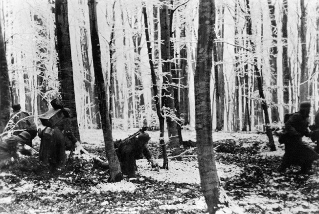 German infantrymen advance through a wooded area during the Ardennes offensive. Hitler threw a force of over 290,000 men at the Americans.