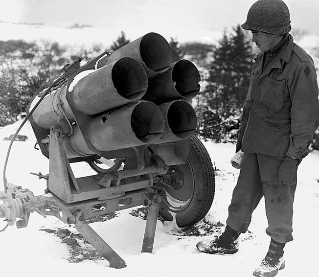 "An American soldier examines a captured multi-barrel rocket launcher known as a Nebelwerfer. The weapon was used extensively against the 106th Division at the beginning of the battle. GIs referred to them as ""Screaming Meemies,"" saying that the psychological effect of this weapon was almost as devastating as the physical effect."