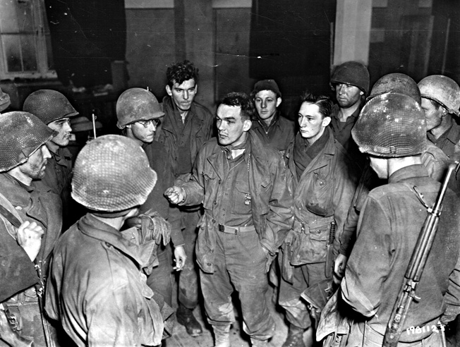 Lieutenant Ivan Long, center, talks to bedraggled members of his Intelligence and Reconnaissance Platoon, 423rd Infantry Regiment, 106th Infantry Division. Trapped by the sudden German assault on December 16, 1944, the platoon traveled over 18 miles back to American lines.